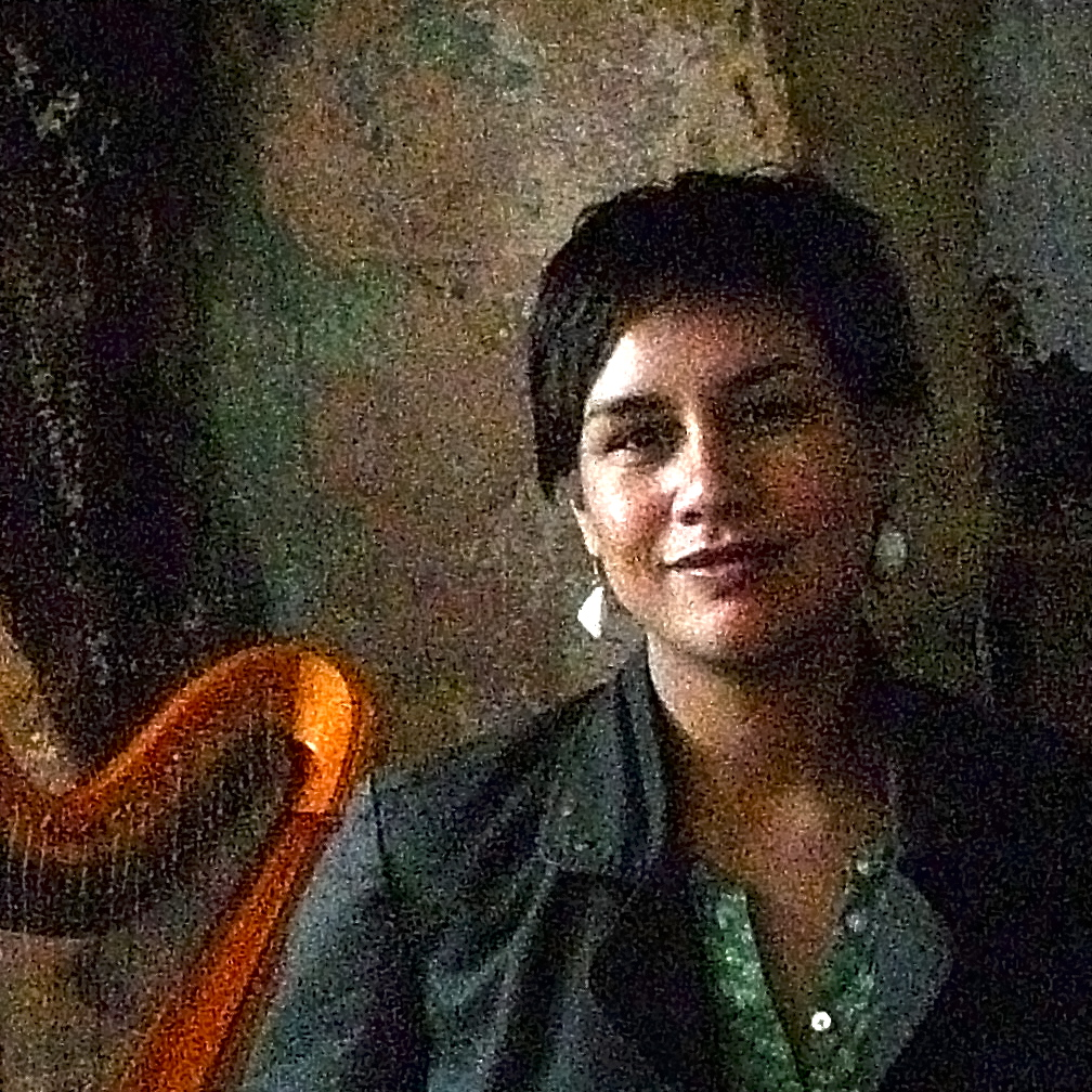 Casual smiling image of Natalia Mann, against a textured wall, harp in background, grainy finish.  Photograph by artist Ferhat Akay.